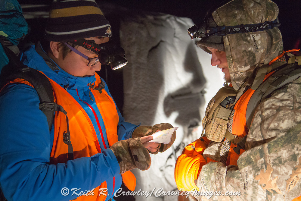 In the pre-dawn glow of a headlamp, Chinese student Li Haoxin (Luke) checks his rifle prior to a hunt for deer and elk with his friend and roommate, Jack Crowley, near Alder, Montana,