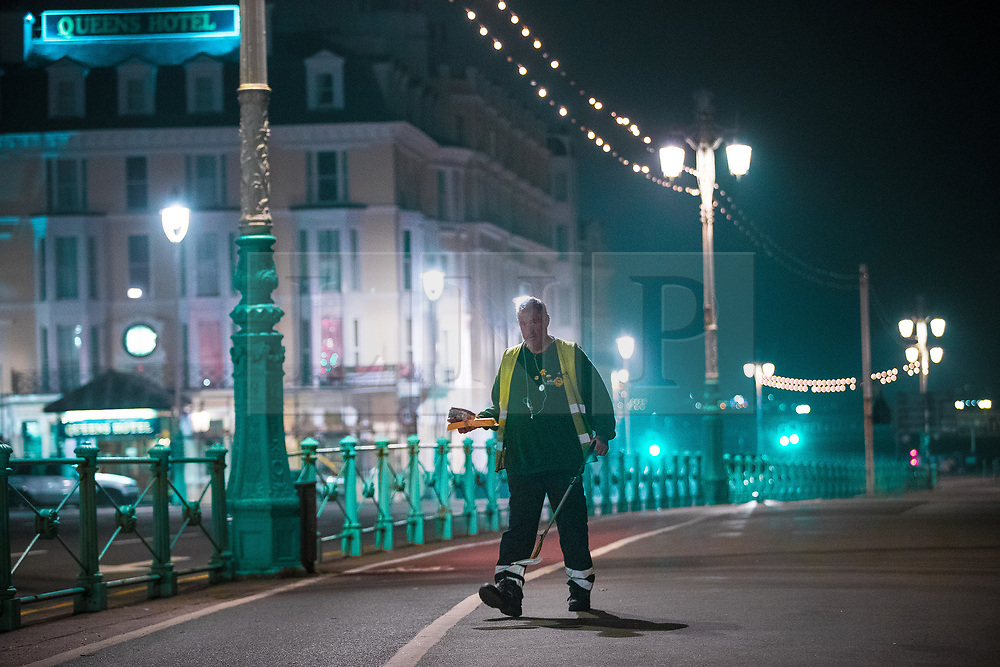 © Licensed to London News Pictures . 26/09/2017. Brighton, UK. A street cleaners working along Brighton Promenade . Revellers at the end of a night out in Brighton during Freshers week , when university students traditionally enjoy the bars and clubs during their first nights out in a new city . Photo credit: Joel Goodman/LNP