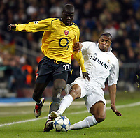 Photo: Chris Ratcliffe.<br /> Real Madrid v Arsenal. UEFA Champions League. 2nd Round, 1st Leg. 21/02/2006.<br /> Julio Cesar Baptista of Real Madrid tussles with Emmanuel Eboue of Arsenal