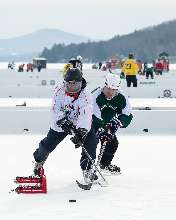Scott Harris of Tavern 27 and Paul Frazer of Crosspoint take to the ice for first round action during the New England Pond Hockey Classic at Meredith Bay Friday morning.  (Karen Bobotas/for the Laconia Daily Sun)