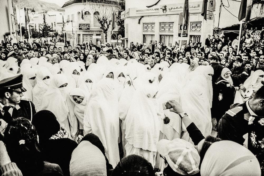 198 / Feier zum Besuch des Koenigs: AFRIKA, MAROKKO, CHEFCHAOUEN, Maerz 2010: In Weiss verschleierte Frauen feiern den Besuch des Koenigs Mohammed VI in Chefchaouen. Chefchaouen, Chaouen oder Xauen ist eine marokkanische Stadt, die Hauptstadt der gleichnamigen Provinz. Sie befindet sich im Nordosten Marokkos, in den Auslaeufern des Rif-Gebirges, in der Naehe von Tetouan. - Marco del Pra / imagetrust - Stichworte: Afrika, Marokko, Maghreb, Maroc, Chefchaouen, Chaouen, Xaouen, Koenigreich, Koenig, Mohammed VI, Medina, Altstadt, Frauen, Schleier, verschleiert, Islam, islamisch, Muslim, muslimisch, Arabisch, Berber,  Religion, Schwarz, Weiss,  Rif, Gebirge, Tradition, Gewand, Feier, Zeremonie, feiern, Besuch, koeniglich, Aufruhr,