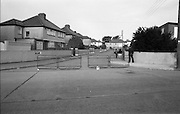 Credit Union Official Shot Dead In Artane. (R63)..1987..25.08.1987..08.25.1987..25th August 1987..While depositing takings in the night safe of Allied Irish Bank in Atrane, Mr Michael Thackaberry was confronted by two armed raiders. The raiders snatched the money and made off on foot. Mr Thackaberry gave chase and was gunned down by one of the raiders as he attempted to recover the money. Mr Thackaberry died at the scene of the shooting...Picture shows a Garda standing watch at Danieli Drive, Artane, the scene of the shooting in which Mr Thackaberry died.