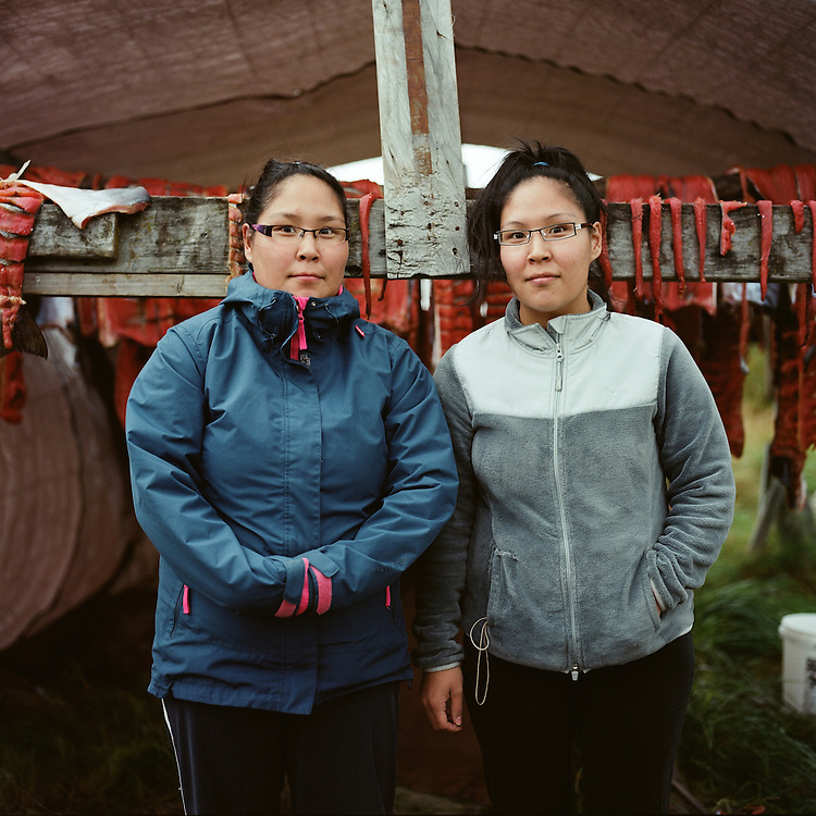 """After cutting the silvers, we put them in salt water and then dry them for three or four days. After drying them, we smoke them and then they will be done. It takes about two weeks from catching them to eating them. It's a passed down recipe."" —Brittany Cleveland & Taryn Andrew are standing in front of traditional Yup'ik fish rack full of silver salmon drying after a successful fishing season in Quinhagak, Alaska. Salmon is an important traditional food resource, not only for nutritional reasons, but culturally and spiritually for Inuit. The Yup'ik word ""Neqa"" means fish and also translates literally to food."