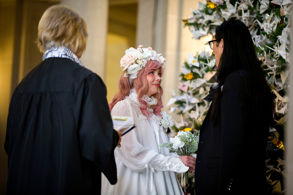 From left: Denise Daley officiates the marriage between Brittany Wood and Adrean Ye at City Hall on Tuesday, Dec. 12, 2017, in San Francisco, Calif.