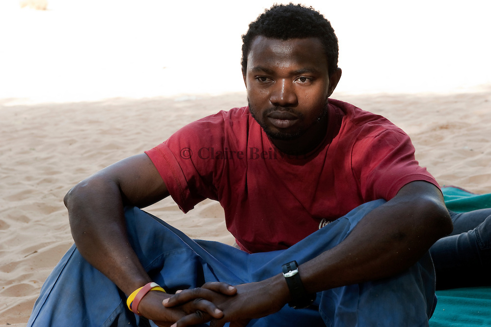 Samuel, a young African migrant from Nigeria back from Libya in an IOM ( International Organization for Migration ) convoy. They are resting under some trees in Archegour in the Ténéré desert. The trip is long and dangerous.