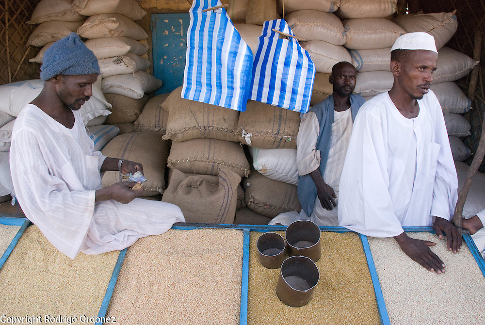 A trader counts money at a market stall selling grain in the town of Abyei.