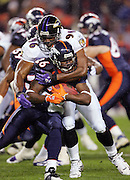DENVER - OCTOBER 9:  Running back Tatum Bell #26 of the Denver Broncos runs the ball and gets tackled by Adalius Thomas #96 of the Baltimore Ravens at INVESCO Field at Mile High on October 9, 2006 in Denver, Colorado. The Broncos defeated the Ravens 13-3. ©Paul Anthony Spinelli *** Local Caption *** Tatum Bell;Adalius Thomas