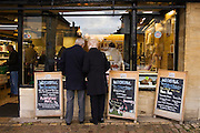 Couple browse the window of a butcher's shop at Burford in the Cotswolds, United Kingdom