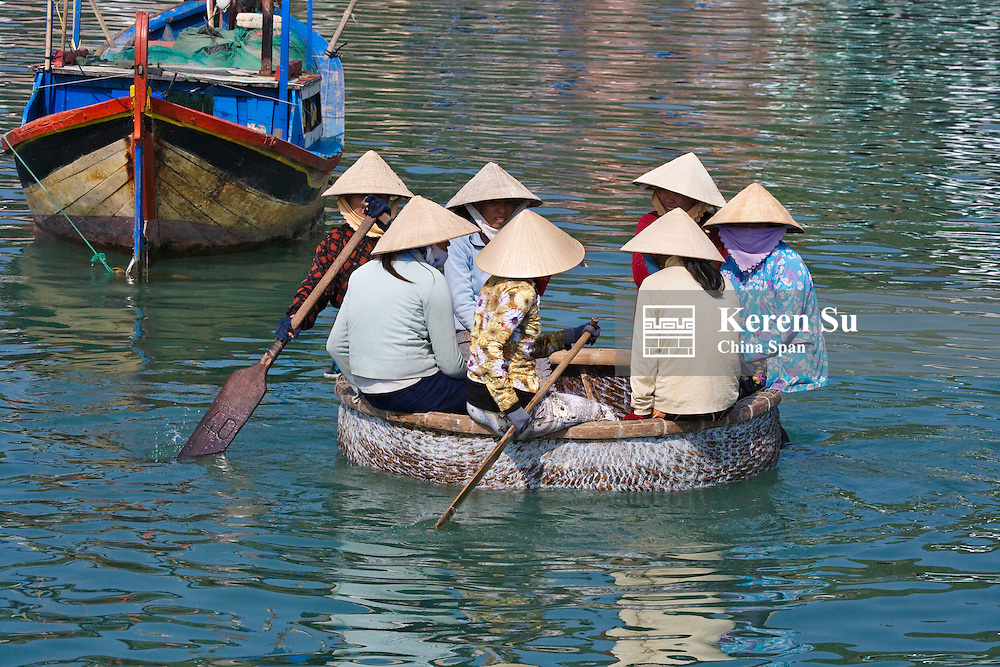 Girl with conical hat in bamboo made basket boat.