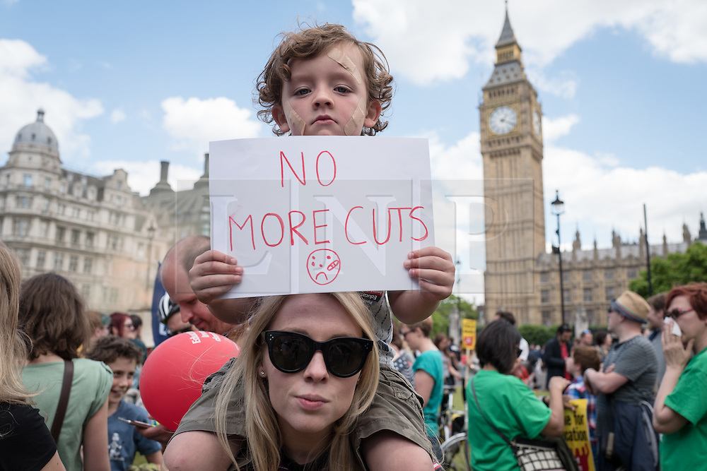 © Licensed to London News Pictures. 05/07/2016. London, UK. Chester, 4, and his mother join thousands of school teachers, parents and children in Parliament Square after striking school teachers marched through central London. The strike, called by the National Union of Teachers (NUT), is in response to cuts to funding and issues with workload, pay and other conditions. Photo credit: Rob Pinney/LNP