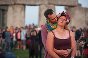 Spiritual revellers celebrate the summer Solstice (mid-summer and longest day) at the ancient stones of Stonehenge, on 21st June 2017, in Wiltshire, England. Fifteen thousand attended the 2017 Solstice at Stonehenge, according to English Heritage. Pagans say the ancient monument is a sacred place that links the Earth, Moon, Sun and the seasons. Built in three phases between 3,000 B.C. and 1,600 B.C. its purpose remains under study. However, it's known that if you stand in just the right place inside the monument on summer solstice, through the entrance towards a rough hewn stone outside the circle you will see the sun rise above the Heel Stone.