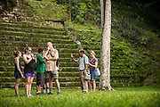 Tourists hiking and exploring the ruins of the ancient Mayan city Tikal lie in present day Guatamala, near the border of Belize.