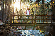 girl on bridge over stream