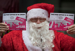 © Licensed to London News Pictures. 19/12/2016. London, UK. Santa Claus joins Post office workers and supporters in a protest outside the Department for Business, Innovation & Skills. Crown Post Offices are being affected during a five day strike by the Communication Workers Union's 3,000 staff at 300 high street branches in a dispute over branch closures, pensions and job losses. Photo credit: Peter Macdiarmid/LNP
