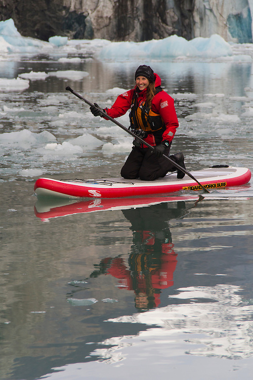 A paddle boarder kneels as she paddles through the ice -- her reflection is beneath her. MR