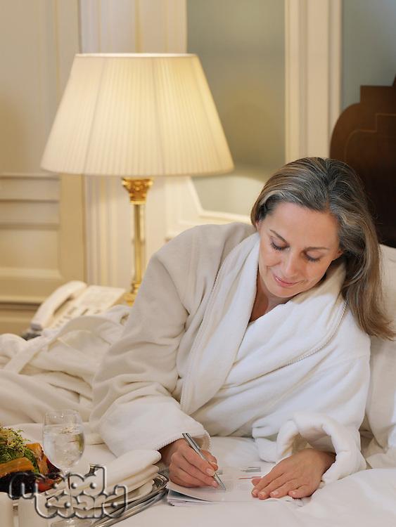 Woman wearing bathrobe writing lying on bed