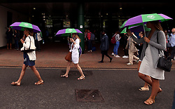 Spectators shelter from the rain on day eight of the Wimbledon Championships at The All England Lawn Tennis and Croquet Club, Wimbledon.