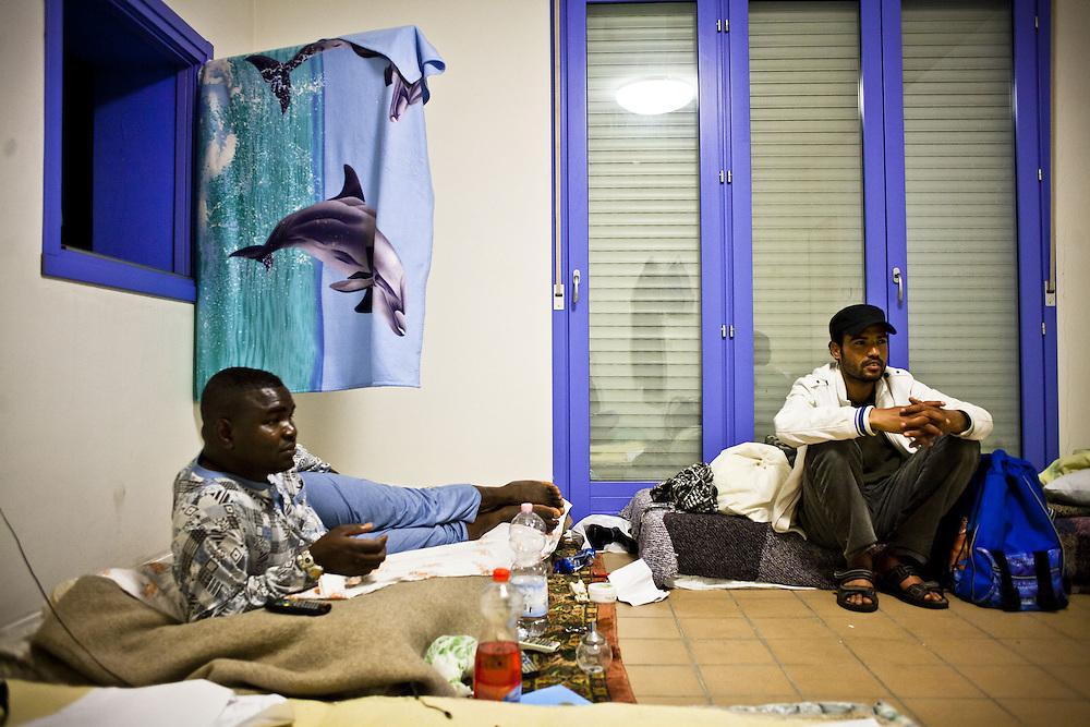 Interno delle ex palazzine olimpiche: due ragazzi sahariani guardano la televisione.