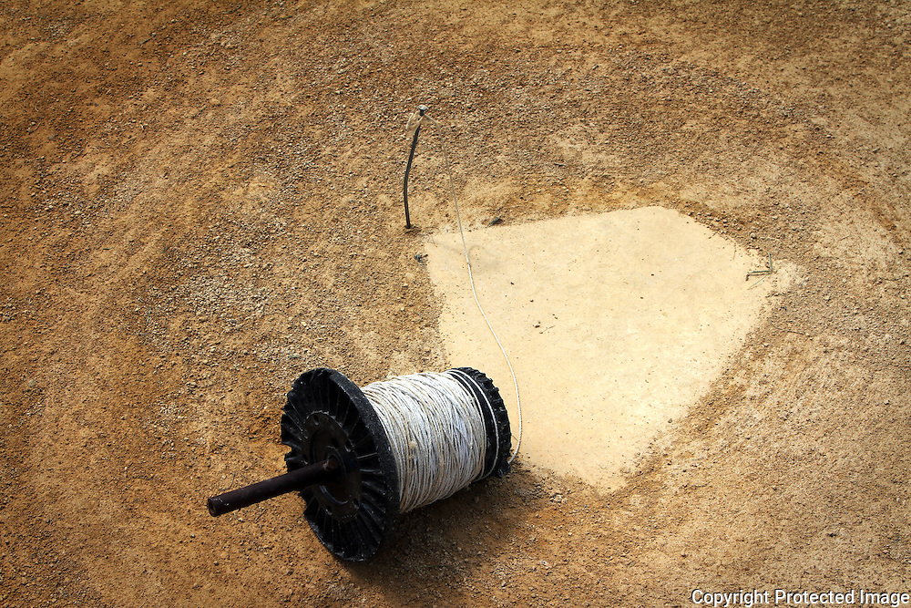 A peg in the ground and a spool of string help keep the first and third base chalk lines straight.  photo by David Peterson