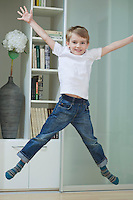 Portrait of a boy in casuals jumping in mid-air at home
