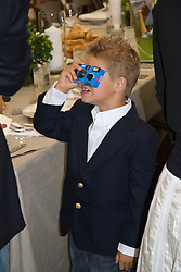 Young boy taking snapshot pictures during a family event