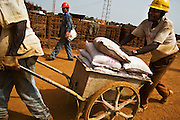 A Chinese worker walks along Guinean workers carrying bags of concrete on the construction site of a new 50,000-seat sports stadium in Conakry, Guinea on Friday March 6, 2009.  The project, an investment of about USD 50 million, is a gift to Guinea from the Chinese government.(Olivier Asselin for the New York Times)