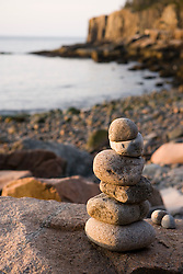 A rock cairn on the cobblestone beach in Momument Cove in Maine's Acadia National Park.  Otter Cliffs are in the distance.
