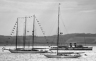 The recently refitted paddle steamer Waverley passes the bunting of Adix a 220' Schooner  and Moonbeam anchored off Largs at the end of the regatta.<br />