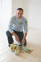 Man kneeling on floor with painting materials