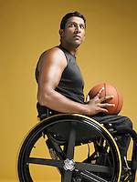 Paraplegic athlete sitting in wheelchair holding basketball side view