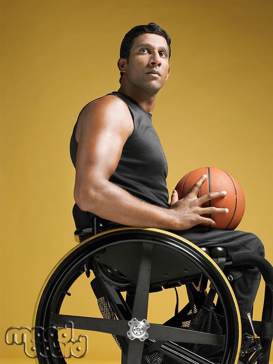Paraplegic athlete sitting in wheelchair holding basketball side view