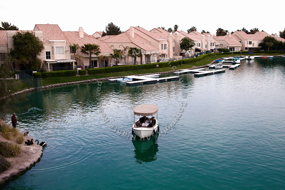People living in Desert Shores, a wealthy residential area hosting various gated communities and artificial lakes, are enjoying their afternoon on a pedal boat (centre) and observing black swans (left) in Las Vegas, Nevada, USA.