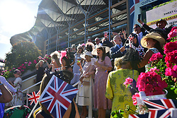 © Licensed to London News Pictures. 21/06/2018. London, UK. Racegoers enjoy Ladies Day at Royal Ascot at Ascot racecourse in Berkshire, on June 21, 2018. The 5 day showcase event, which is one of the highlights of the racing calendar, has been held at the famous Berkshire course since 1711 and tradition is a hallmark of the meeting. Top hats and tails remain compulsory in parts of the course. Photo credit: Ben Cawthra/LNP