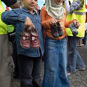 Children gathering children shoes to remember the children killed of Israeli bombardments. Protest against the war in Lebanon, Edinburgh Scotland 12 July 2006.<br />