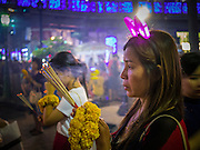 "31 DECEMBER 2012 - BANGKOK, THAILAND: Thais pray for a prosperous New Year on New Year's Eve at the Erawan Shrine in the Ratchaprasong Intersection in Bangkok. Many Thais go to Buddhist temples and shrines to ""make merit"" for the New Year. The traditional Thai New Year is based on the lunar calender and is celebrated in April, but the Gregorian New Year is celebrated throughout the Kingdom, especially in larger cities and tourist centers, like Bangkok, Chiang Mai and Phuket. The Bangkok Countdown 2013 event was called ""Happiness is all Around @ Ratchaprasong."" All of the streets leading to Ratchaprasong Intersection were closed and the malls in the area stayed open throughout the evening.    PHOTO BY JACK KURTZ"