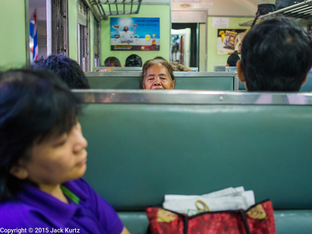 20 MARCH 2015 - BANGKOK, THAILAND:    A passenger sleeps on a third class train leaving Bangkok for Kabin Buri. The State Railways of Thailand (SRT), established in 1890, operates 4,043 kilometers of meter gauge track that reaches most parts of Thailand. Much of the track and many of the trains are poorly maintained and trains frequently run late. Accidents and mishaps are also commonplace. Successive governments, including the current military government, have promised to upgrade rail services. The military government has signed contracts with China to upgrade rail lines and bring high speed rail to Thailand. Japan has also expressed an interest in working on the Thai train system. Third class train travel is very inexpensive. Many lines are free for Thai citizens and even lines that aren't free are only a few Baht. Many third class tickets are under the equivalent of a dollar. Third class cars are not air-conditioned. PHOTO BY JACK KURTZ