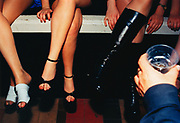 Women's Legs in Assorted Shoes and Hand Holding Drink