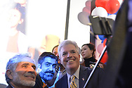 Garden City, New York, USA. November 6, 2018. Nassau County Democrats watch Election Day results at Garden City Hotel, Long Island. To the right of man holding selfie stick is (wearing yellow tie) Suffolk County Executive STEVE BELLONE.