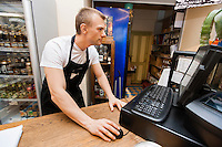 Portrait of salesman using computer at cash counter in supermarket