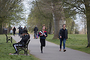 As the second week of the Coronavirus lockdown continues and a week before Easter when Prime Minister Boris Johnson reminds Britons to stay locally and not to travel to beauty spots, the UK death toll rises to 2,921, with 1m cases of Covid-19 worldwide in 181 countries. As Londoners enjoy sunshine and spring temperatures, a runner passes pedestrians in Brockwell Park in Herne Hill, 3rd April 2020, in south London, England.