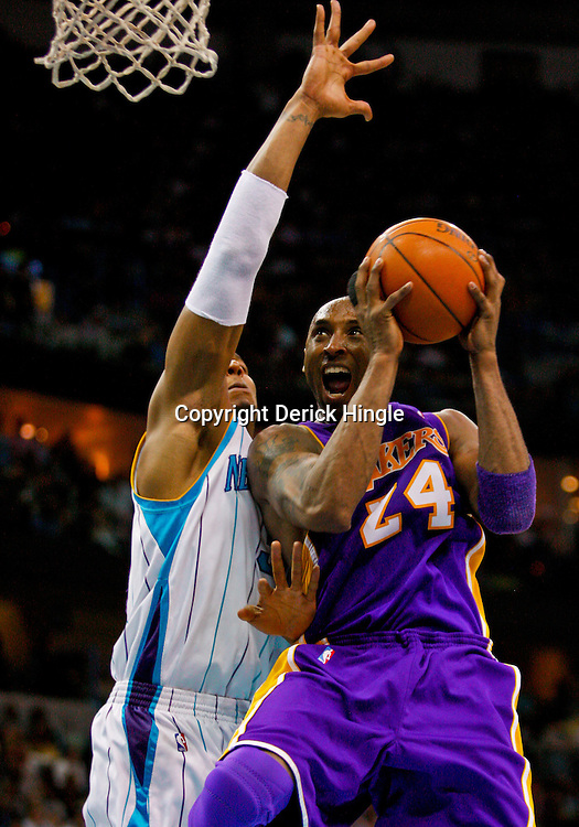 Mar 29, 2010; New Orleans, LA, USA; Los Angeles Lakers guard Kobe Bryant (24) shoots and draws a foul from New Orleans Hornets forward David West (30) during the second half at the New Orleans Arena. The Hornets defeated the Lakers 108-100. Mandatory Credit: Derick E. Hingle