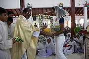 Members of the Afro-Sri Lankan community give offerings to Father Kennedy at St Mary's Church on the event of the 500 year celebration held on September 24th. The date of the event was decided by them and roughly relates to the time they believe the first African slaves were brought to the Island by the Portuguese at the beginning of the 16th Century. It began with Sunday Mass at the Church.<br /> <br /> Out of all communities of African diaspora that surround the Indian Ocean those of Sri Lanka are by far the smallest and most fragile, first brought by the Portuguese, the Dutch and eventually the British as slaves.<br /> <br /> After the Abolition of the Slave Trade Act was passed in the British Parliament in 1807, the process of putting an end to slavery began in British controlled countries. On being emancipated most Africans stayed and a century ago the Afro-Sri Lankan population was believed to be around 6000 people. Today that number has dwindled to less than 500 and are likely to totally disappear in a few generations.
