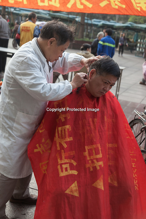 China, Shanghai. red Cross day on Nanjing street; Street hairdresser