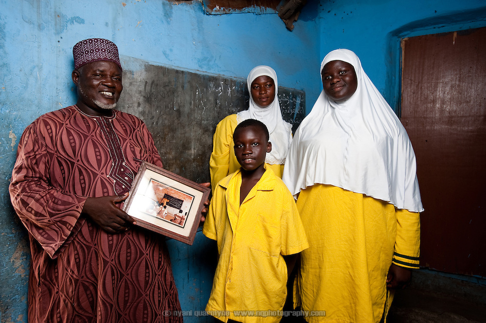 Mohammed Mustapha Yadjalal founded a school in his Nima home in 1984. In 1986, when it reached the point that he had 400 students in his home, the school moved to its present site, and was later taken over by the Islamic Education Unit of the Ghana Education Service. Students learn Arabic and Islamic studies from 8:00 - 10:00am, and then a conventional English curriculum from 10:00am - 3:00pm. Here he is pictured with students in a room in his home that was once a classroom.