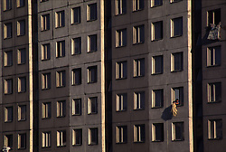 SLOVAK REPUBLIC BRATISLAVA PETRZELKA AUG96 - A woman dusts her bedroll out of one of the many windows of this concrete housing block. This style of architecture was referred to as Socialist Functionalism during the communist years. jre/Photo by Jiri Rezac<br /><br />© Jiri Rezac 1996<br /><br />Tel:   +44 (0) 7050 110 417<br />Email: info@jirirezac.com<br />Web:   www.jirirezac.com