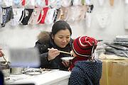 Woman feeds a baby with chinese sticks at a clothes shop in the Chinese district, Milan Jannuary 26, 2004. ..26 JAN 2004 MILAN : INTERNO DI NEGOZIO DI ABBIGLIAMENTO FEMMINILE IN VIA BRAMANTE, NEL QUARTIERE CINESE. DONNA IMBOCCA UN BAMBINO CON LE BACCHETTE.
