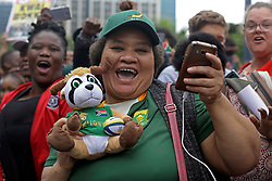 Monday 11th November 2019.<br /> City Hall, Grand Parade,<br /> And City Centre, Cape Town,<br /> Western Cape,<br /> South Africa.<br /> <br /> SPRINGBOKS CELEBRATE WINNING THE RUGBY WORLD CUP CHAMPIONSHIP IN 2019 WITH A COUNTRYWIDE VICTORY TOUR!<br /> <br /> SPRINGBOKS RUGBY WORLD CUP VICTORY TOUR CAPE TOWN!<br /> <br /> An excited female fan wearing her Springbok jersey and carrying a Springbok soft toy and taking photos and selfies while she celebrates along with many others as the Springboks drive past in their open top bus in the Cape Town City Centre.<br /> <br /> The reigning Rugby World Cup Champions namely the South African Springbok Rugby Team, celebrates winning the Webb Ellis Cup during the International Rugby Football Board Rugby World Cup Championship held in Japan in 2019 with their Victory Tour that culminated in the final city tour taking place in Cape Town. Thousands of South African fans filled the streets of the city all trying their best to show their support for their beloved Springboks and to celebrate them winning the Rugby World Cup for the third time. South Africa previously won the Rugby World Cup in 1995, 2007 and now again in 2019. South African Springbok Captan Siya Kolisi took the opportunity to speak to the gathered crowd about how something like this brings unity and that we should live together as a nation that practices what is known as ubuntu. Ubuntu is a quality that includes the essential human virtues of compassion and humanity. This image taken in Cape Town on Monday 11th November 2019.<br /> <br /> This image is the property of Seven Bang Media Group (Pty) Ltd, hereinafter referred to as SBM.<br /> <br /> Picture By: SBM / Mark Wessels. (11/11/2019).<br /> +27 (0)61 547 2729<br /> mark@sevenbang.com<br /> www.sevnbang.com<br /> <br /> Copyright © SBM. All Rights Reserved.