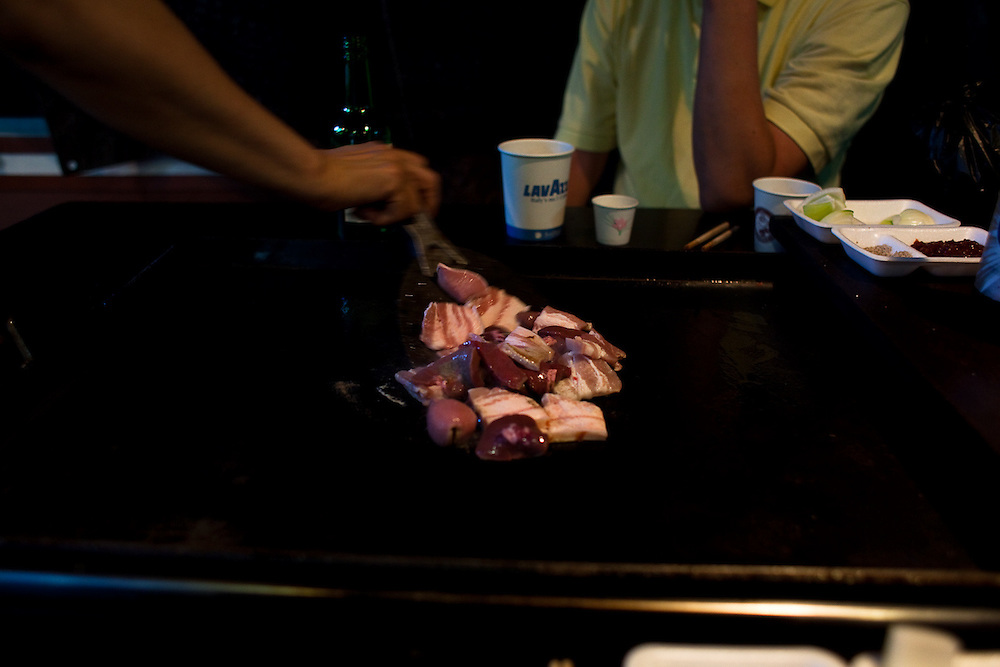 Bacon liver and kidneys on the grill at a food stand in a Seoul market.