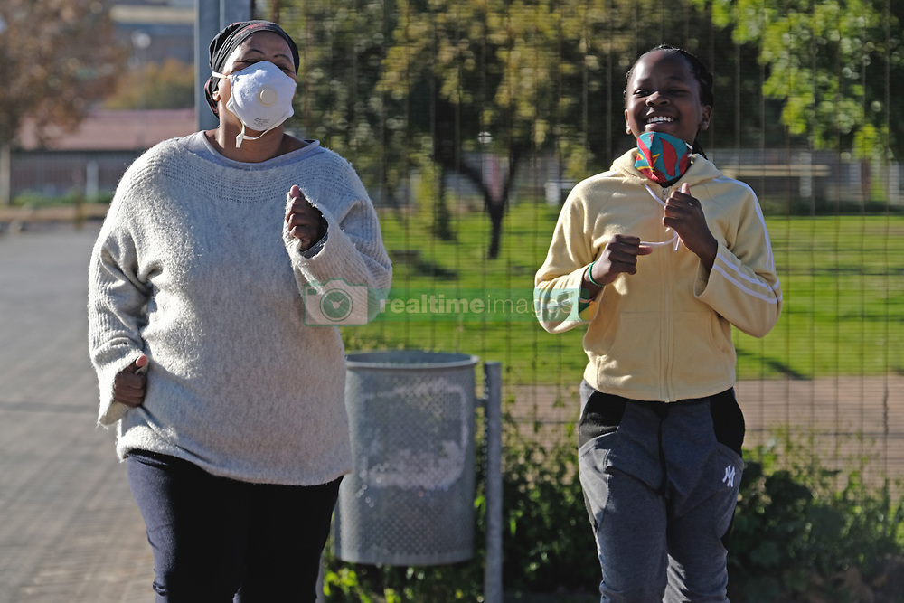 JOHANNESBURG, SOUTH AFRICA - MAY 10: Family members exercising together in Ellis Park during lockdown level 4 on May 10, 2020 in Johannesburg, South Africa. According to media reports, during lockdown level 4 people are allowed to exercise. Guidelines allow for cycling, running and walking as examples and must be within a 5km radius of their residences between 6:00 am – 9:00 am. (Photo by Dino Lloyd)