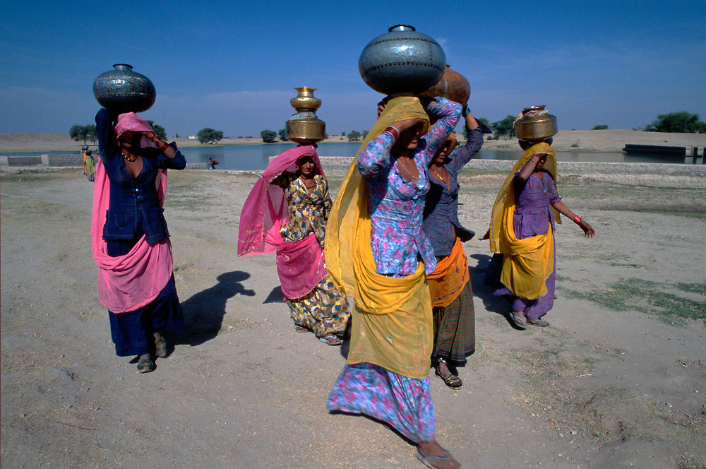 14 Dec 1995, Silgau, near Khimsar, Rajasthan, India --- Rajasthnai women carry brass containers of water away from an oasis. Silgau, near Khimsar, Rajasthan, India. --- Image by © Jeremy Horner/CORBIS